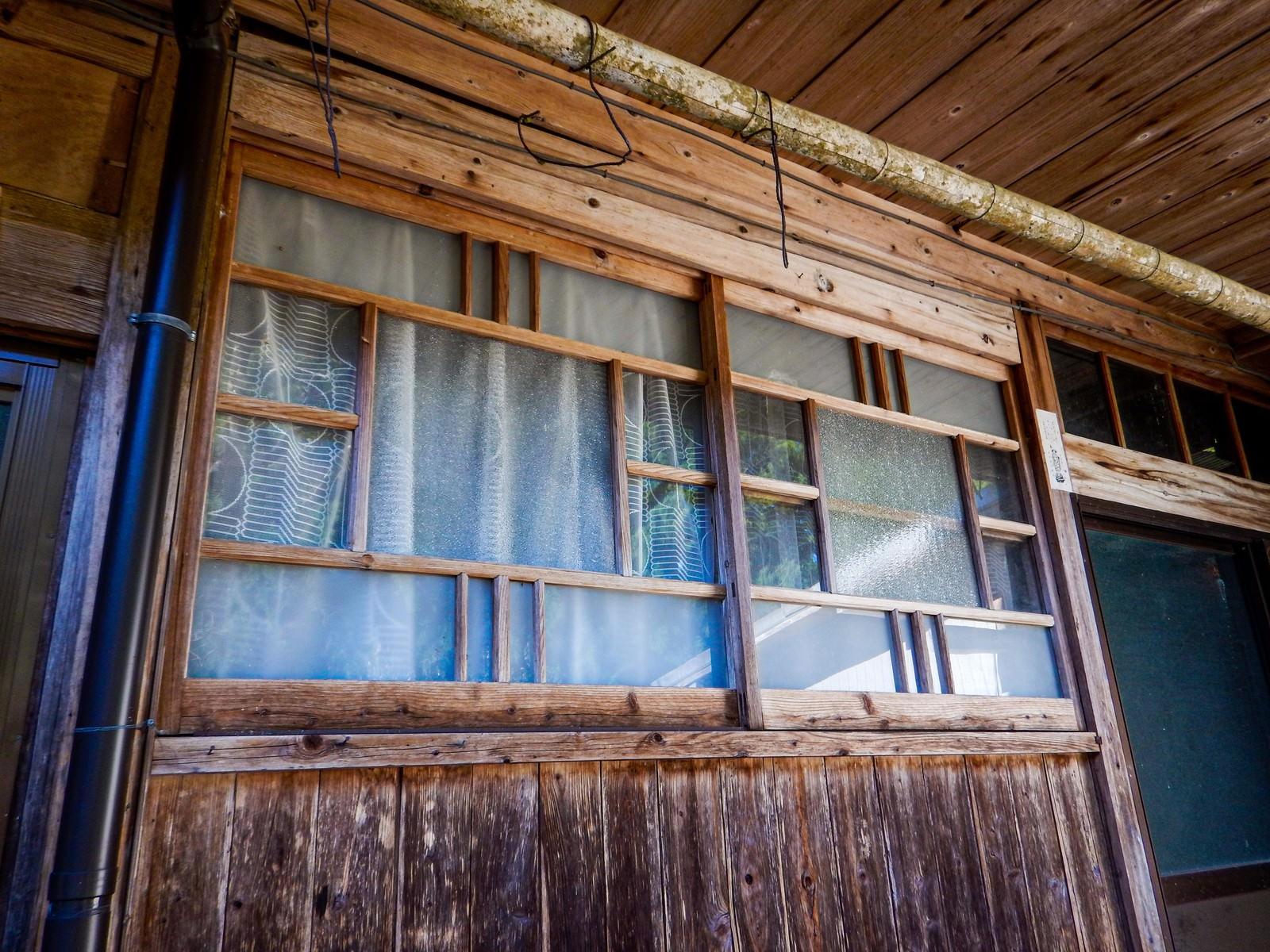 「廃屋の軒下にある窓」の写真