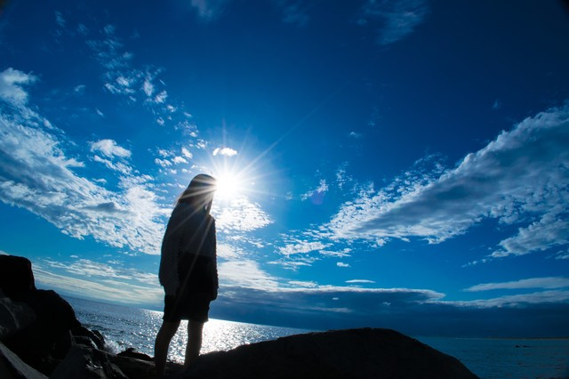 海岸に立つ女性のシルエットの写真