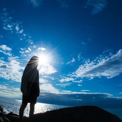 「海岸に立つ女性のシルエット」の写真素材