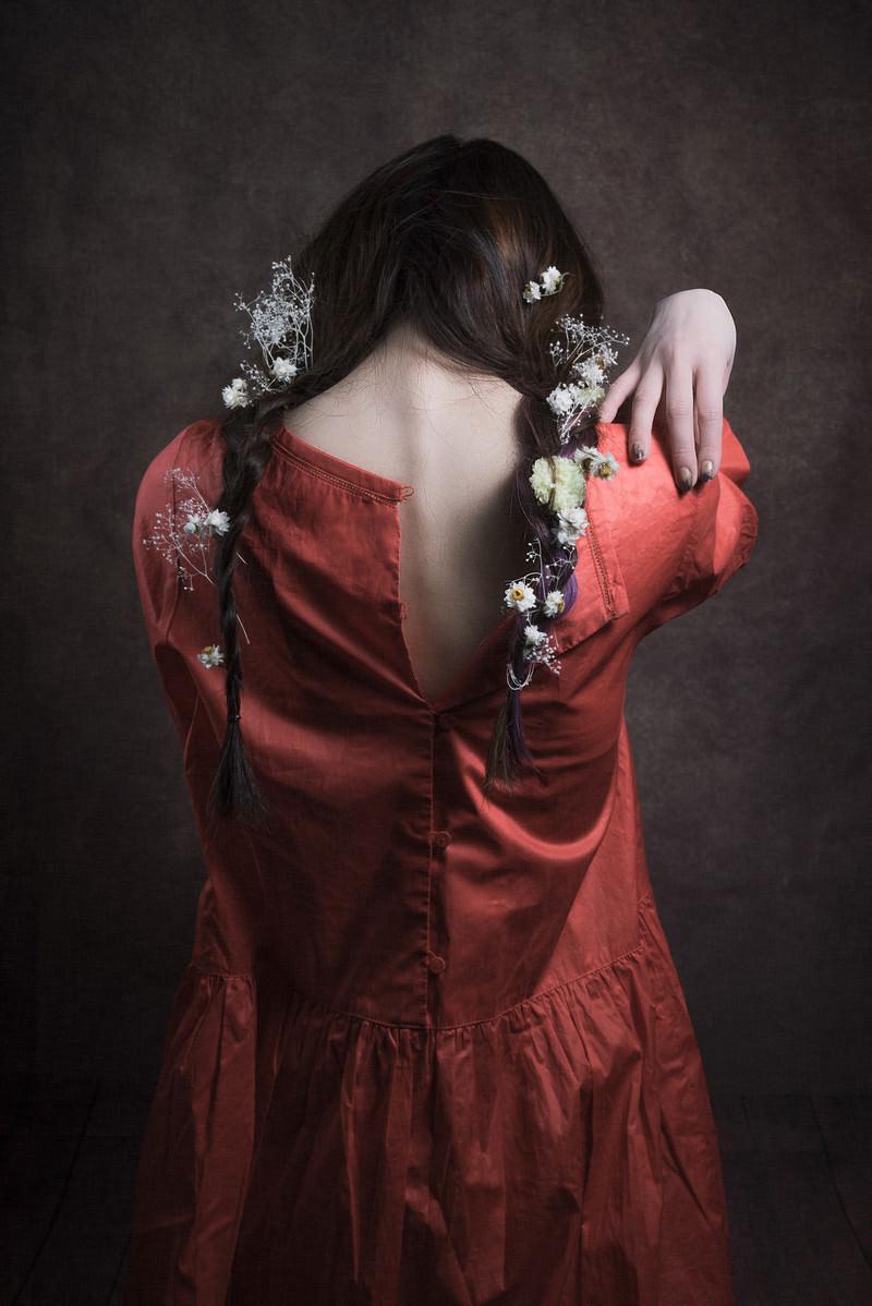 「背中ファスナーに手を伸ばす三編みの女性モデル」の写真