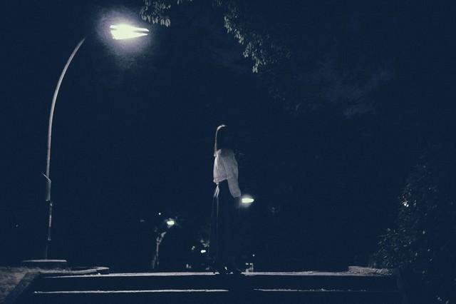 深夜に徘徊する女性の後姿の写真