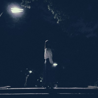 深夜の街灯のあかりと女性の写真