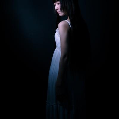 暗闇の中、うっすらとした女性の後ろ姿の写真