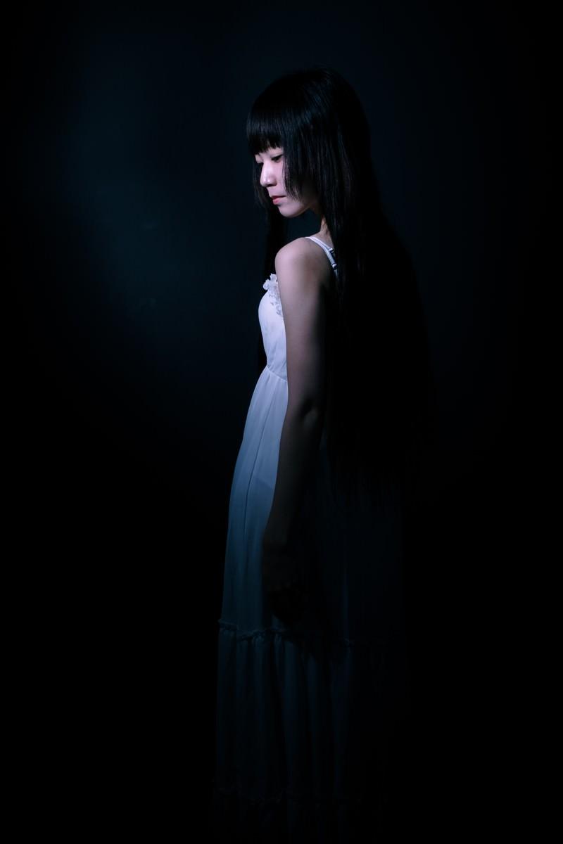 「暗闇の中、うっすらとした女性の後ろ姿」の写真[モデル:緋真煉]