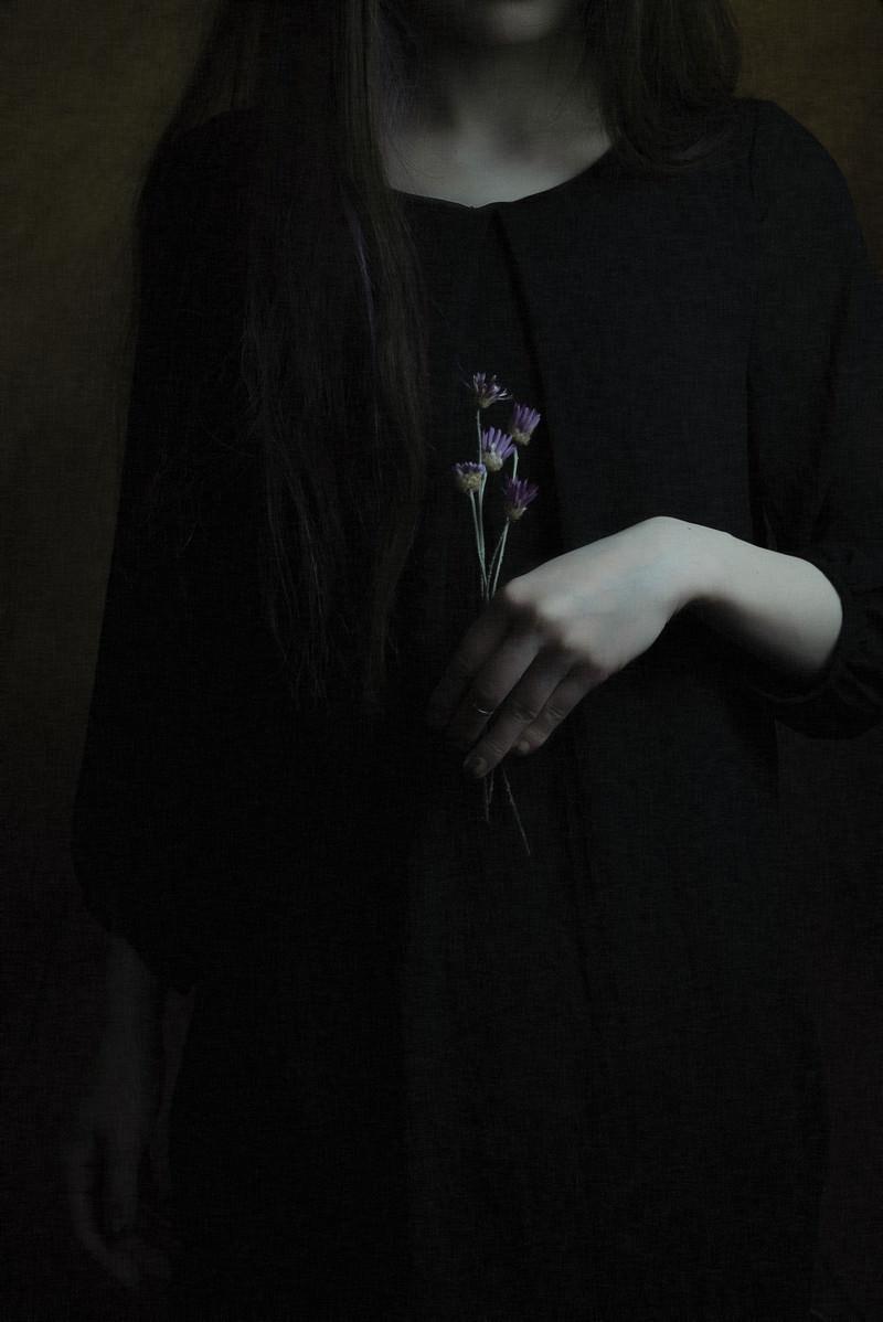 「紫色の造花を持つ黒ワンピースの女性」の写真