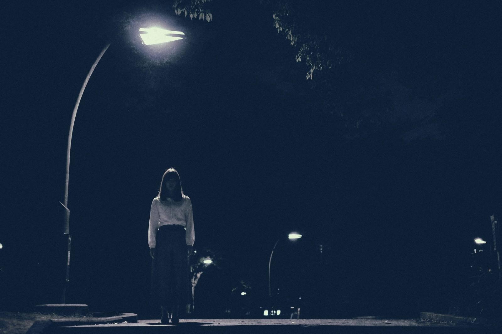 「街灯の下からこちらを見つめる女性」の写真[モデル:さとうゆい]