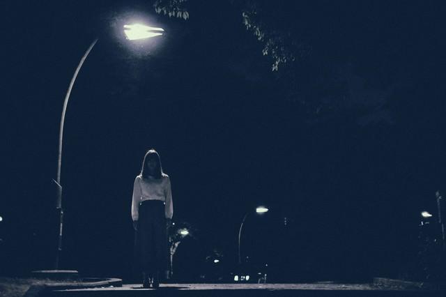 街灯の下からこちらを見つめる女性の写真