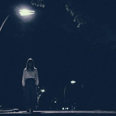 「街灯の下からこちらを見つめる女性」の写真素材