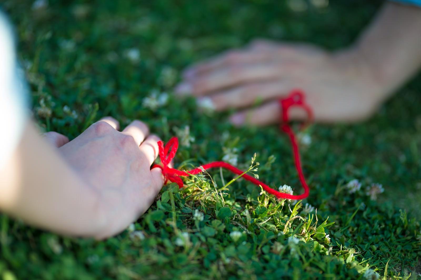 「赤い糸でつながれた女性と男性の手」の写真