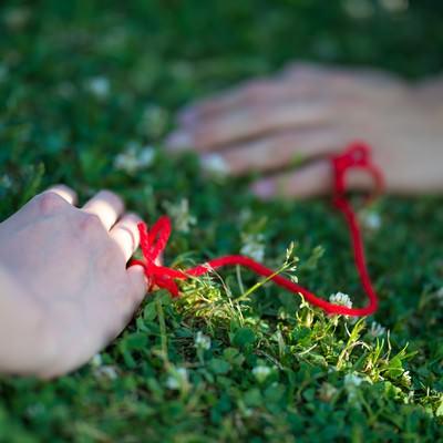 「赤い糸でつながれた女性と男性の手」の写真素材
