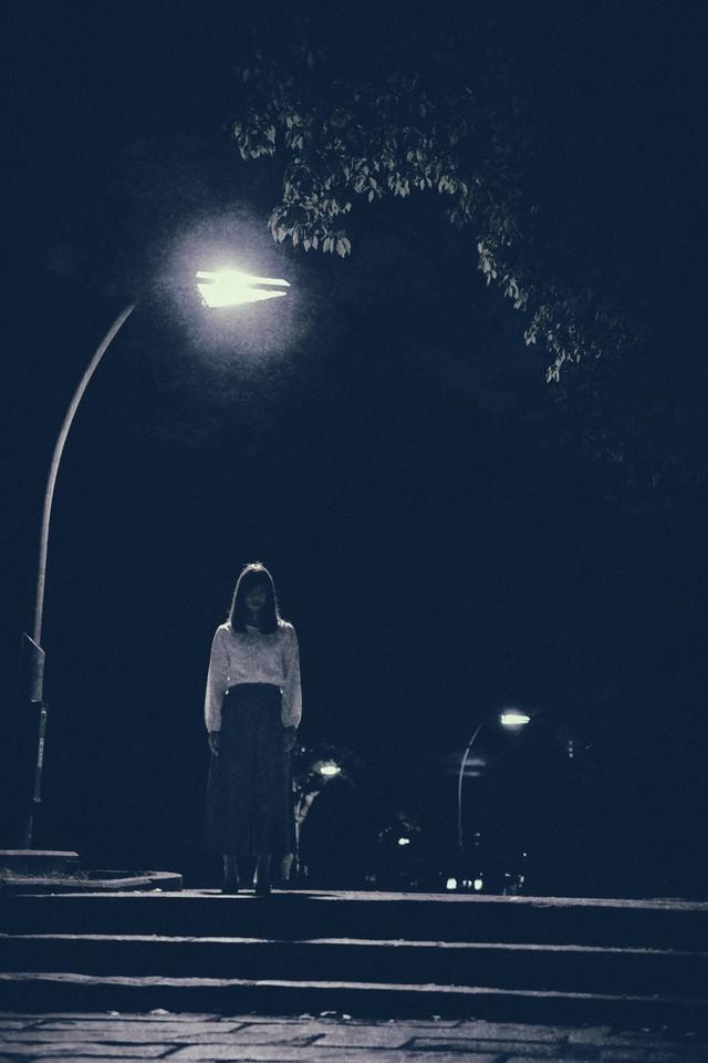 街灯の下で待ち続ける女性の写真