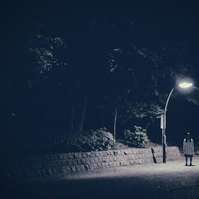 「実際にあった怖い話系に使いやすい。街灯下の女性」の写真素材