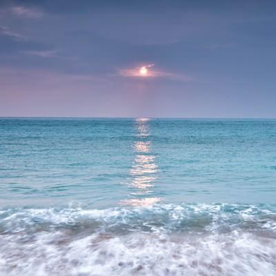 青い海に映える太陽の写真