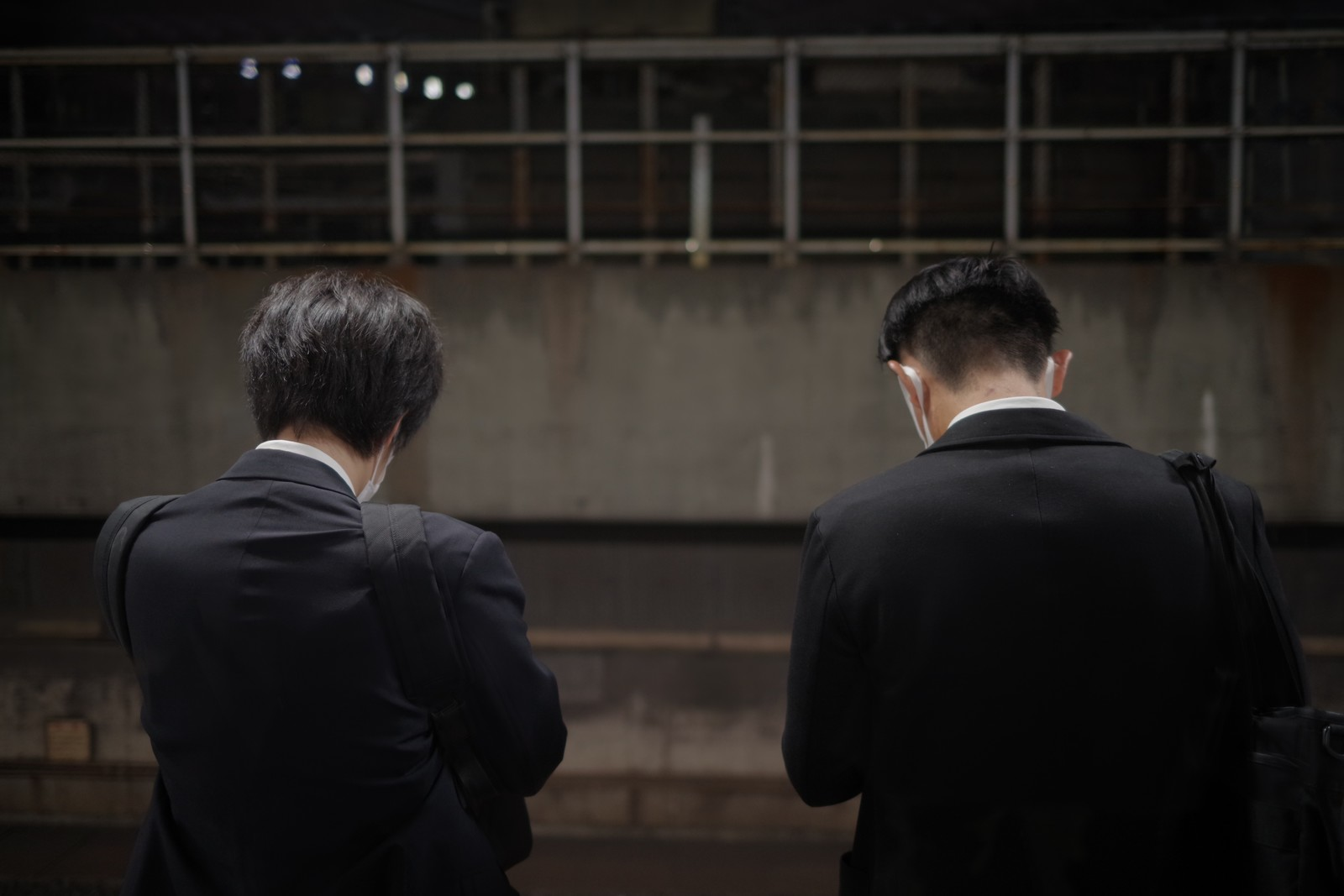 「電車を待つサラリーマンの後ろ姿」の写真