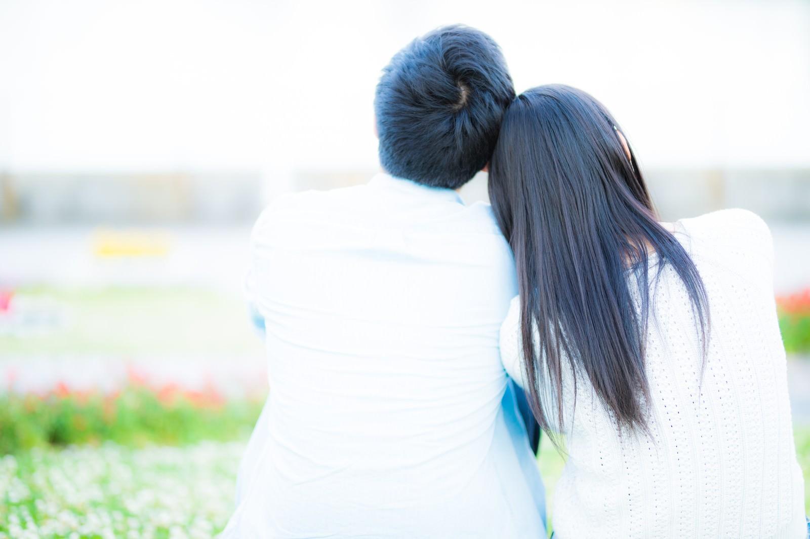 「肩を寄せる男女の後ろ姿」の写真