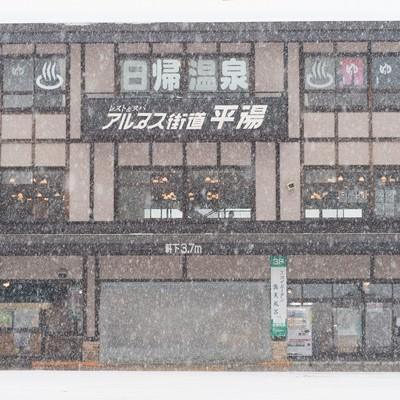 「雪が降る平湯温泉バスターミナル前」の写真素材