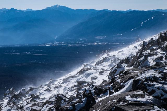 「身が凍える寒さと強風で舞い上がる雪の白煙」のフリー写真素材