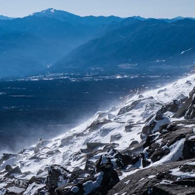 身が凍える寒さと強風で舞い上がる雪の白煙の写真