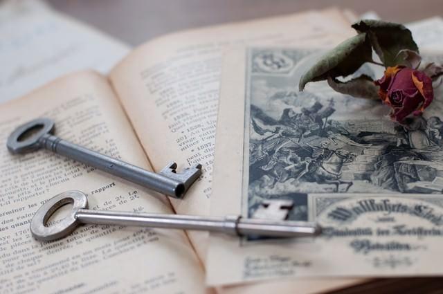 朽ちたバラと古い鍵の写真