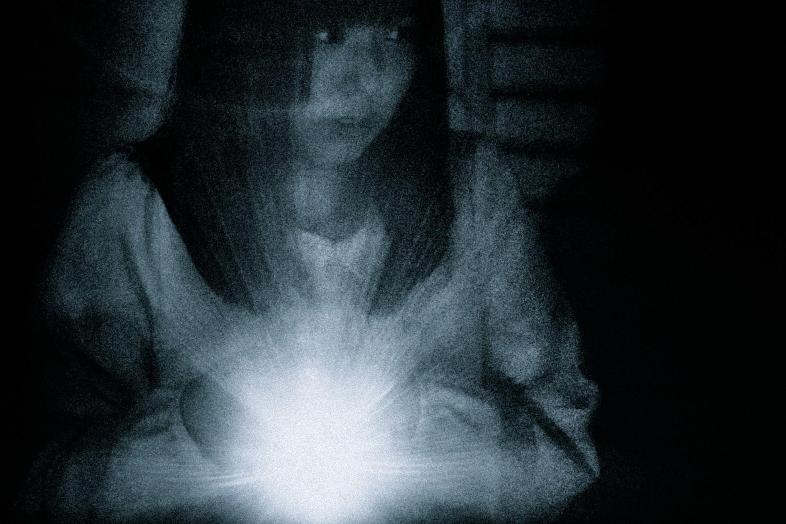 「少しずつ、ゆっくり、慎重に、警戒しながら。ライトの光を頼りに探索する女性」の写真[モデル:さとうゆい]