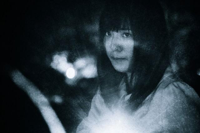 不安な面持ちで暗闇を進む女性の写真