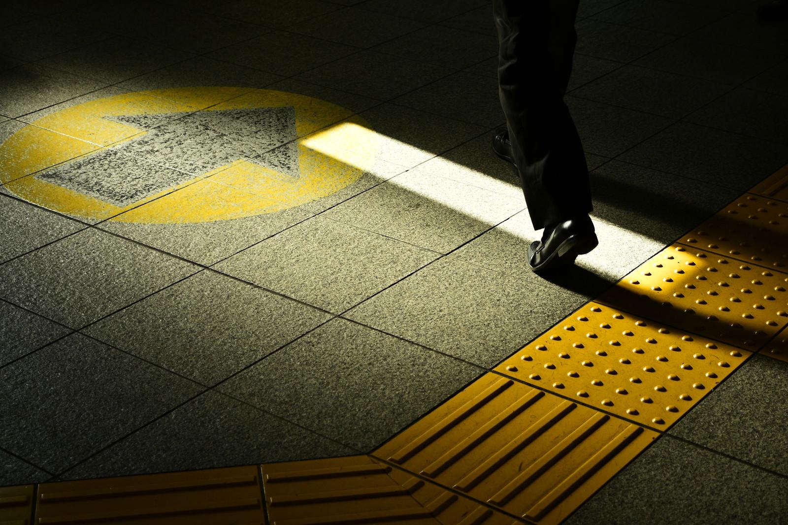 「通勤中のサラリーマンの足元と点字ブロック」の写真