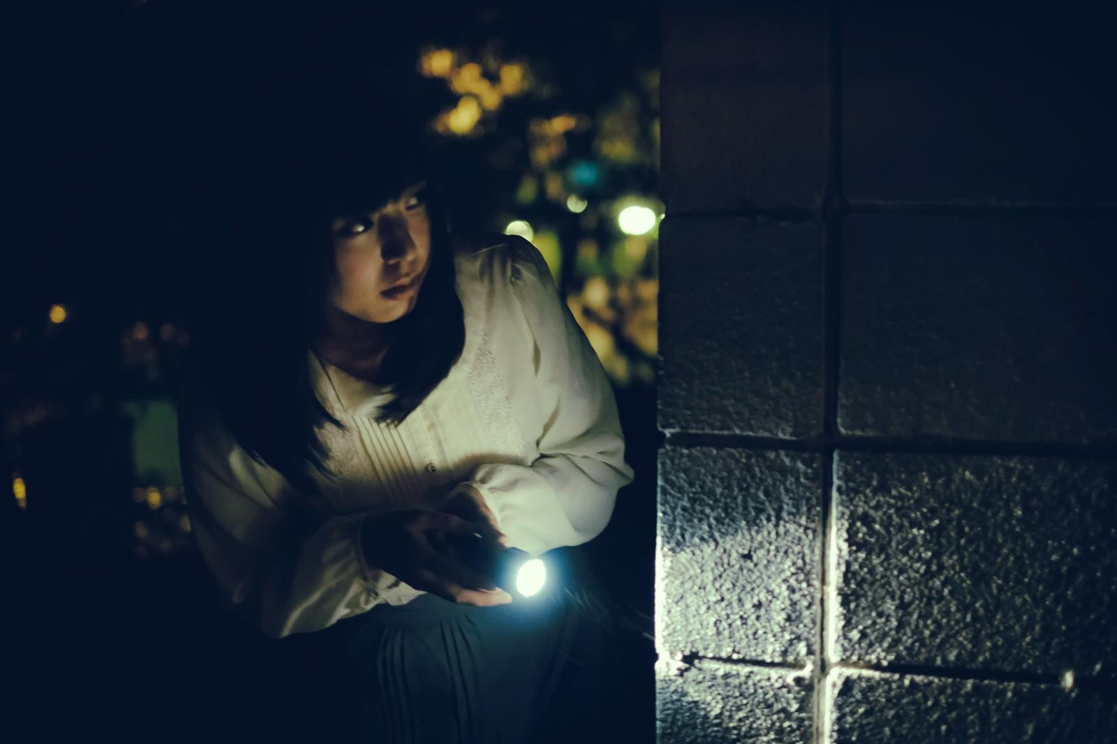 「深夜に物音がしたから懐中電灯を持って確認しに来た女性(死亡フラグ)」の写真[モデル:さとうゆい]