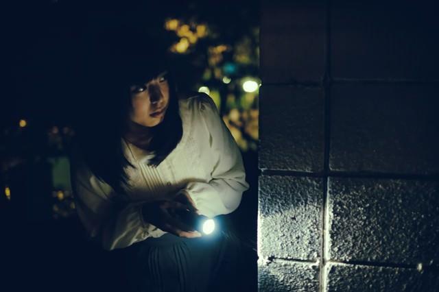 深夜に物音がしたから懐中電灯を持って確認しに来た女性(死亡フラグ)の写真