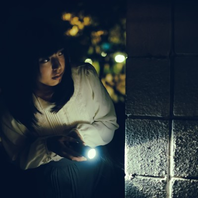 「深夜に物音がしたから懐中電灯を持って確認しに来た女性(死亡フラグ)」の写真素材
