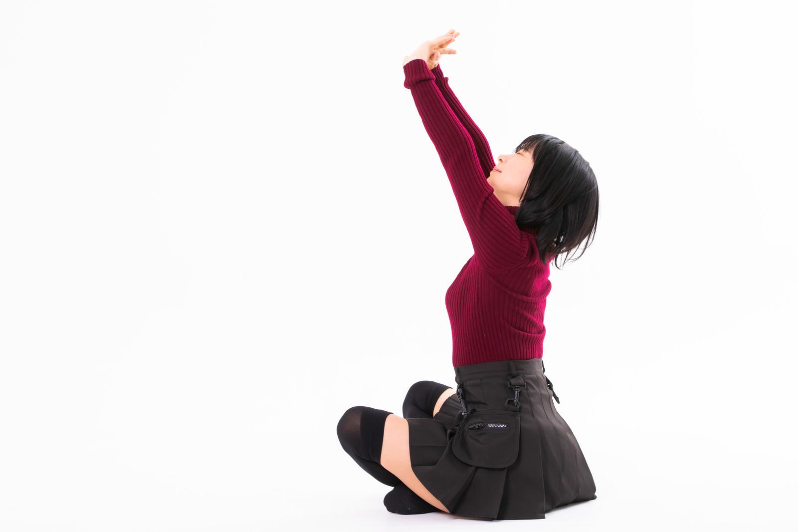 「胡坐をかいて伸びをする女性」の写真[モデル:にゃるる]