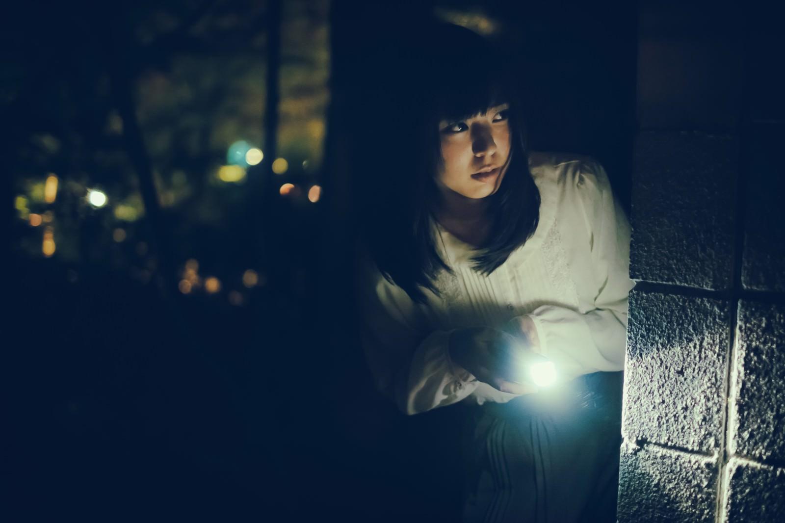 「暗闇の中、ハンドライトを照らす肝試し女子」[モデル:さとうゆい]