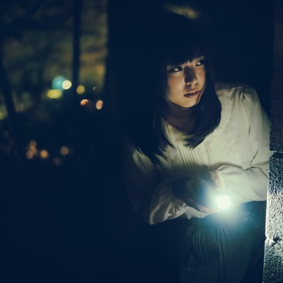 「暗闇の中、ハンドライトを照らす肝試し女子」の写真素材
