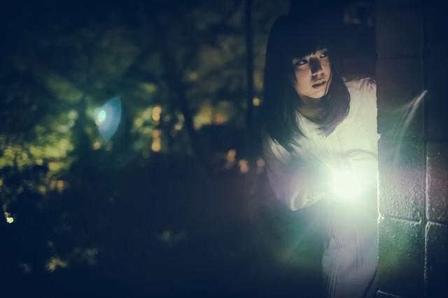 懐中電灯で辺りを警戒する女性の写真