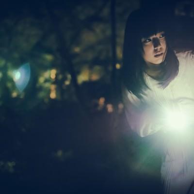 「懐中電灯で辺りを警戒する女性」の写真素材