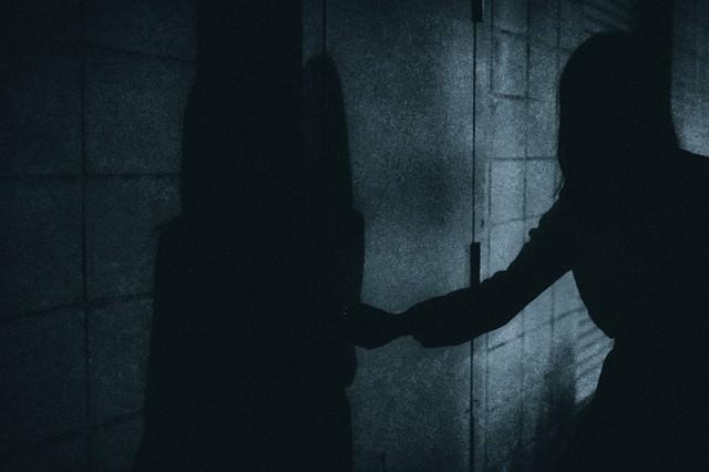 扉をあける人影の写真
