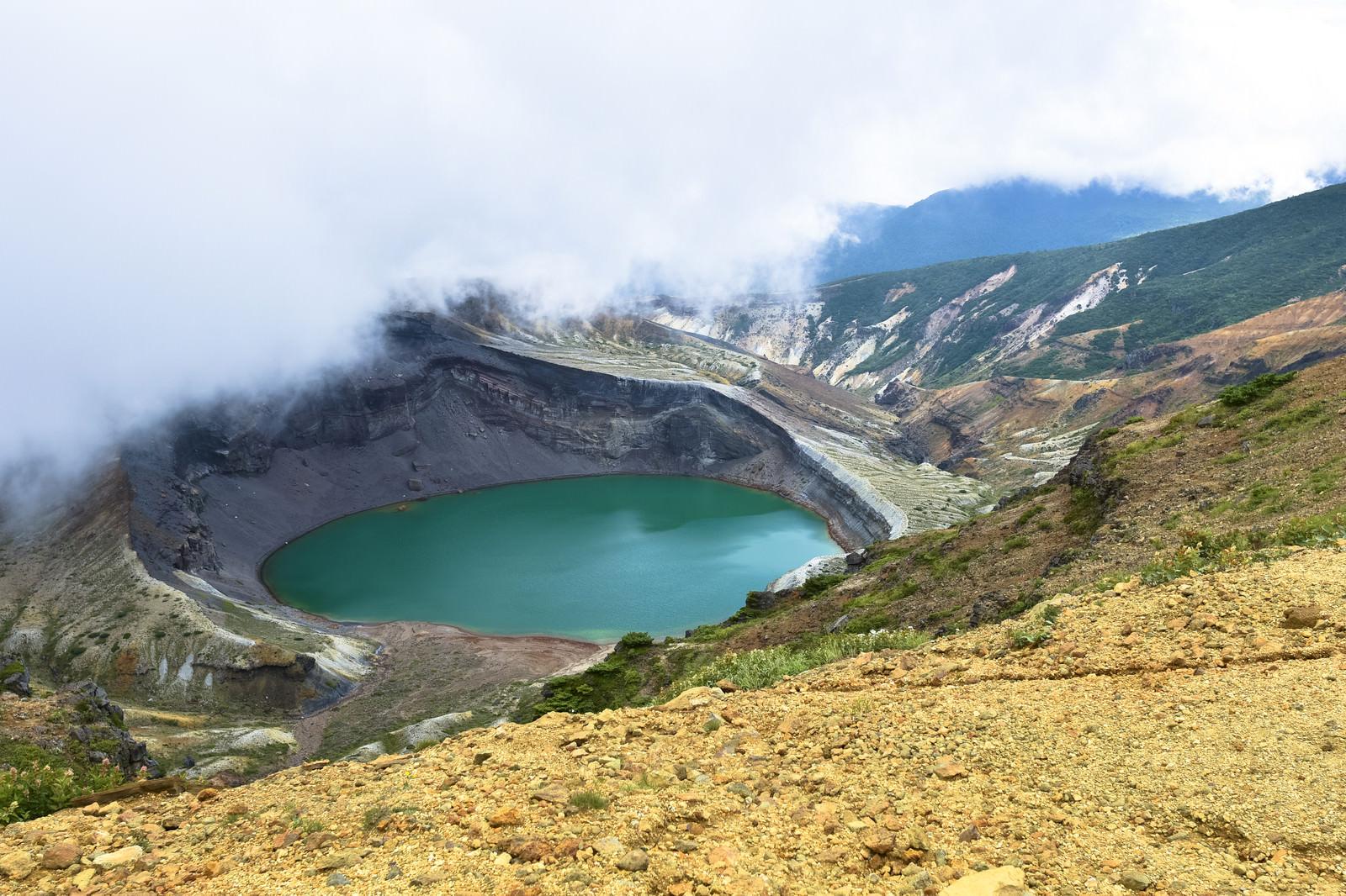 「雲の合間に除くエメラルドグリーンの火山湖(蔵王山)」の写真