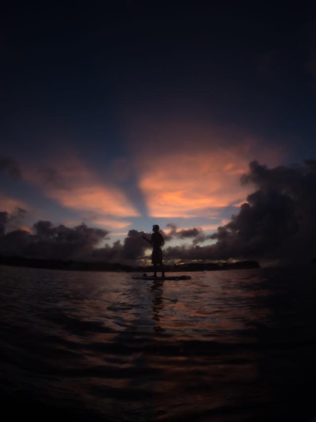 夕暮れにパドルボートを漕ぐ青年のシルエットの写真