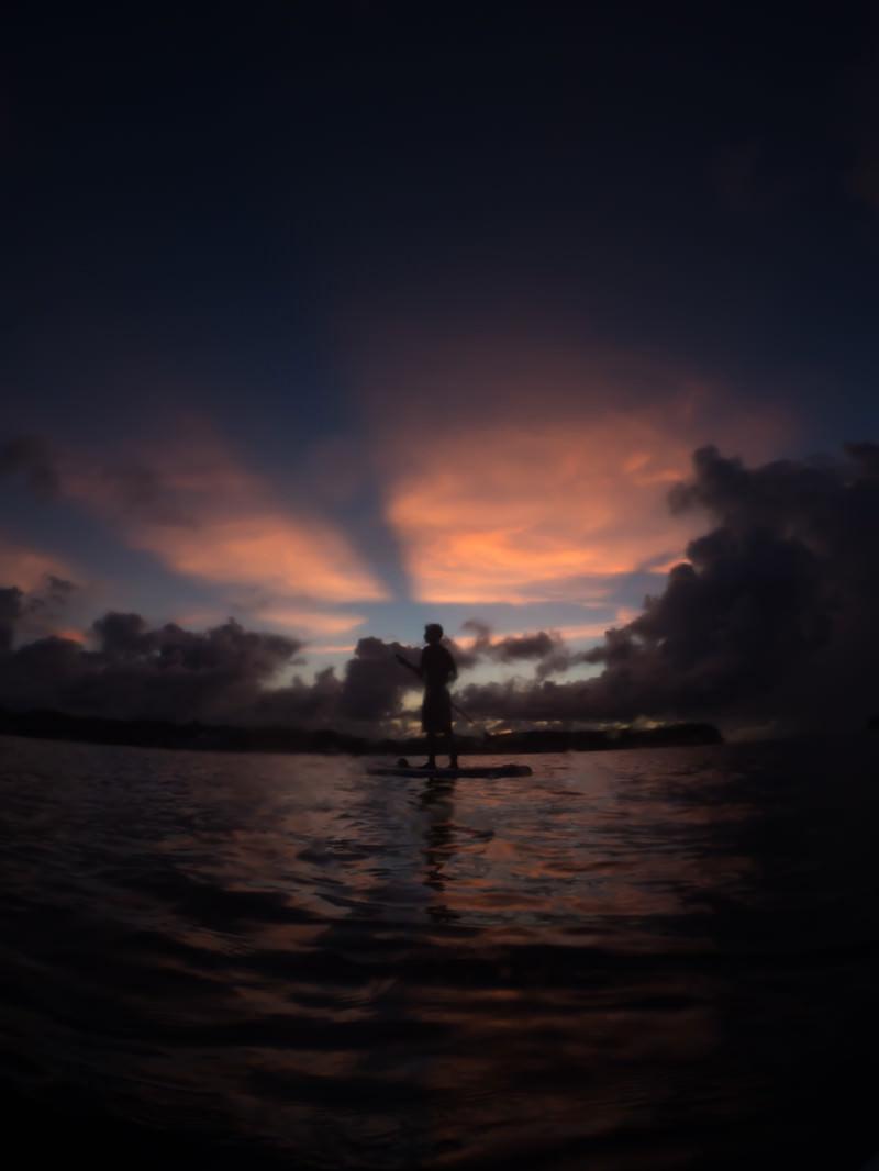 「夕暮れにパドルボートを漕ぐ青年のシルエット」の写真