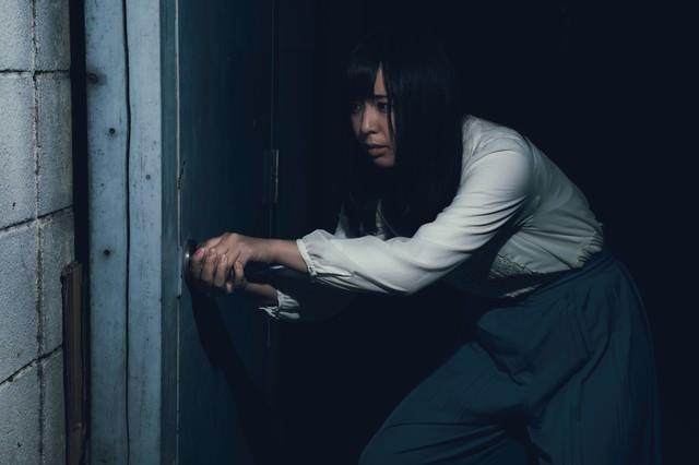古びたドアを恐る恐る開ける女性の写真