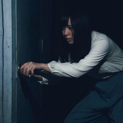 「古びたドアを恐る恐る開ける女性」の写真素材