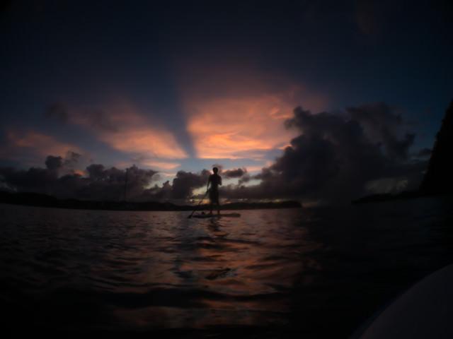 夕暮れ時にイカダを漕ぐ少年のシルエットの写真