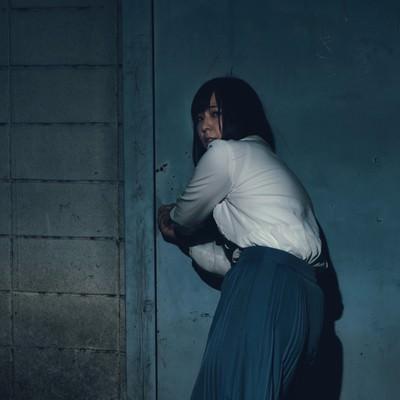 「何かに追おわれて廃屋に逃げこもうとする女性」の写真素材