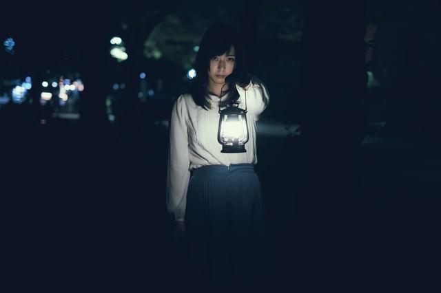 真夜中ランタンを手にした若い女性の写真