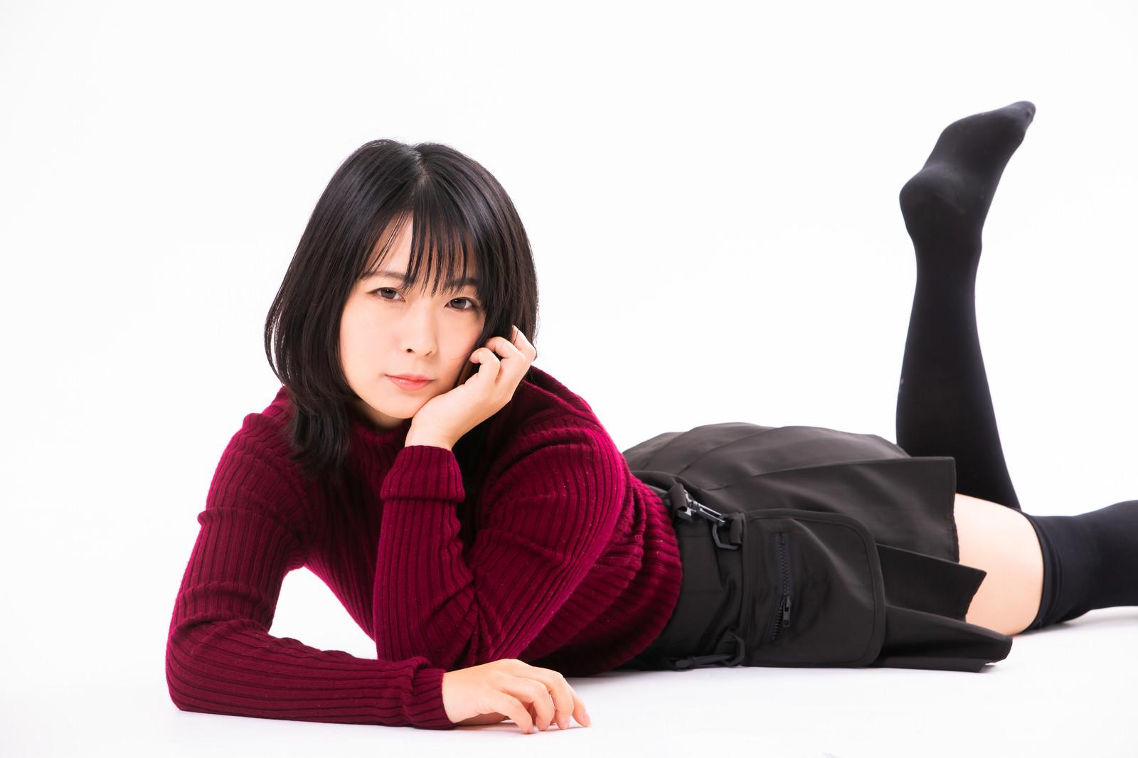 「頬杖を突いて横たわる女性」の写真[モデル:にゃるる]