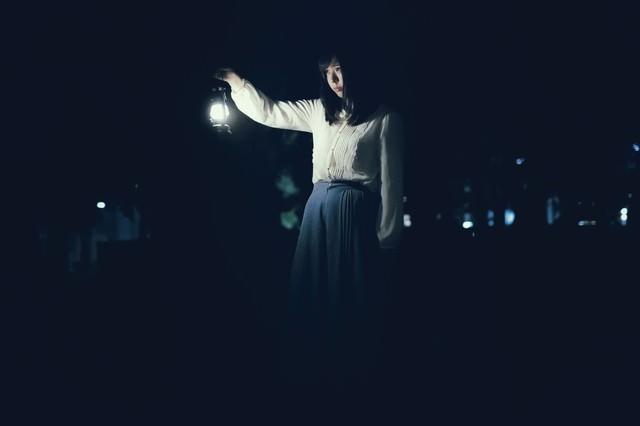 ランタンを持ち歩く女性の写真
