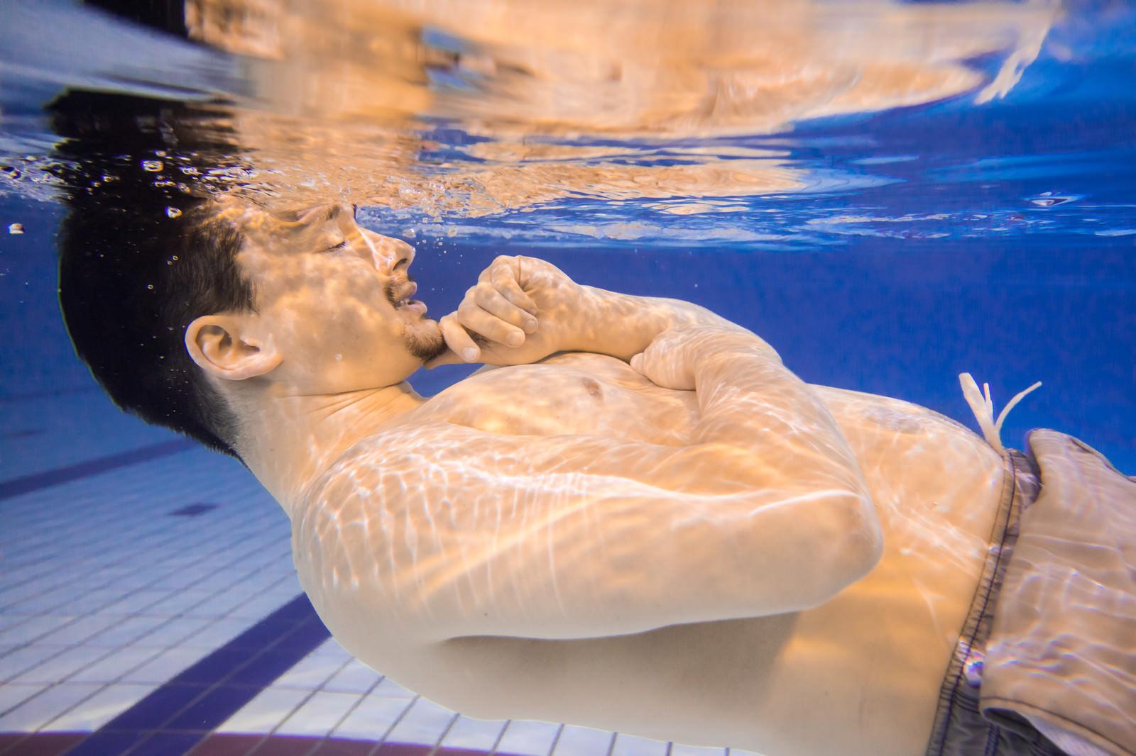 「ぽっこりお腹を気にしてプールから出てこない男性」の写真[モデル:Max_Ezaki]