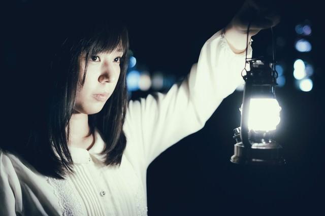 夜に明かりを灯すランタンと女性の写真
