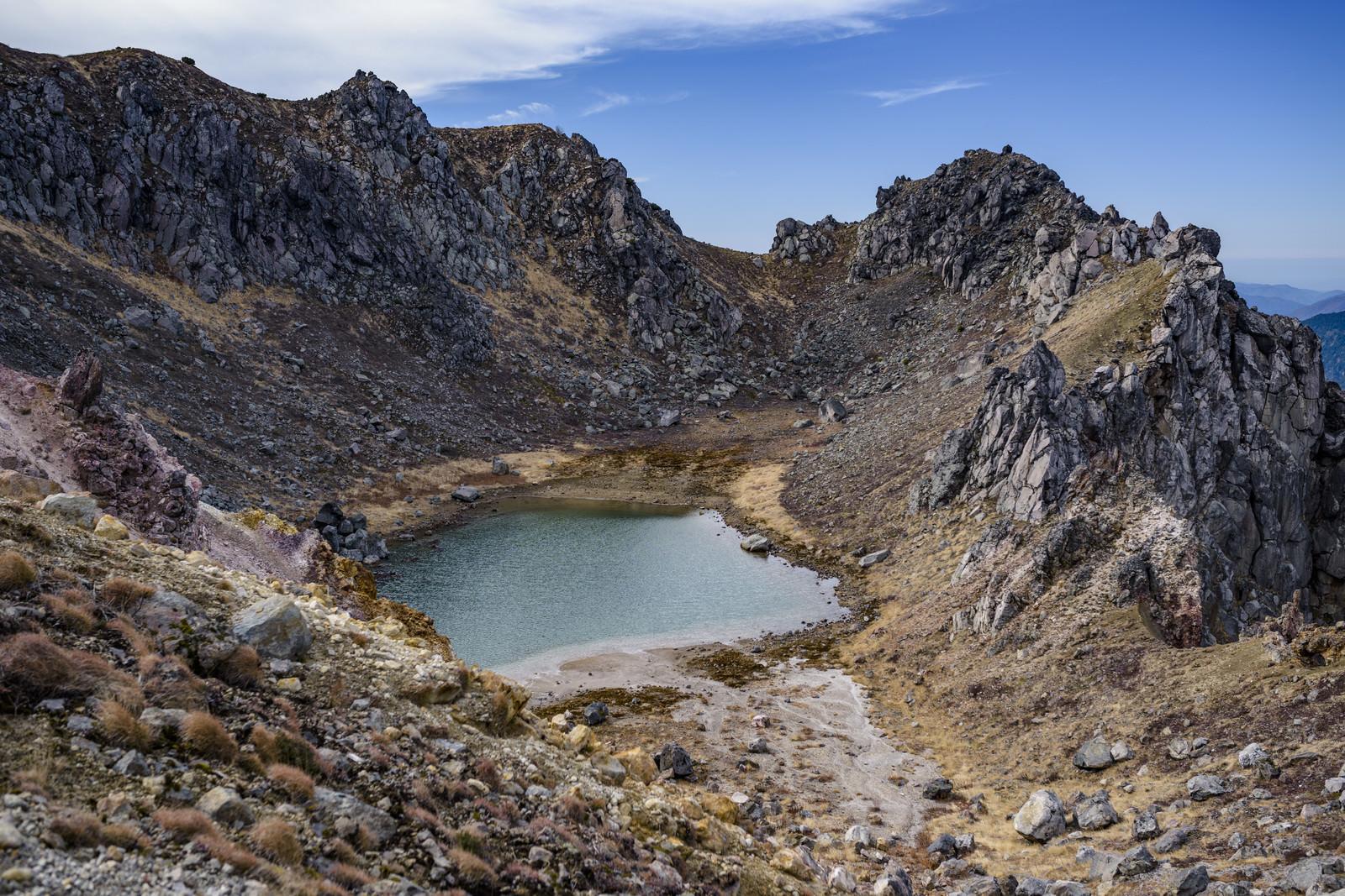 「火山性の岩に囲まれた山頂の火山湖」の写真