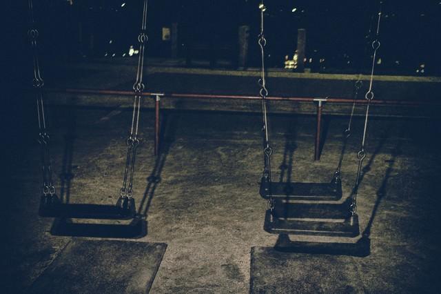 深夜の公園のブランコの写真