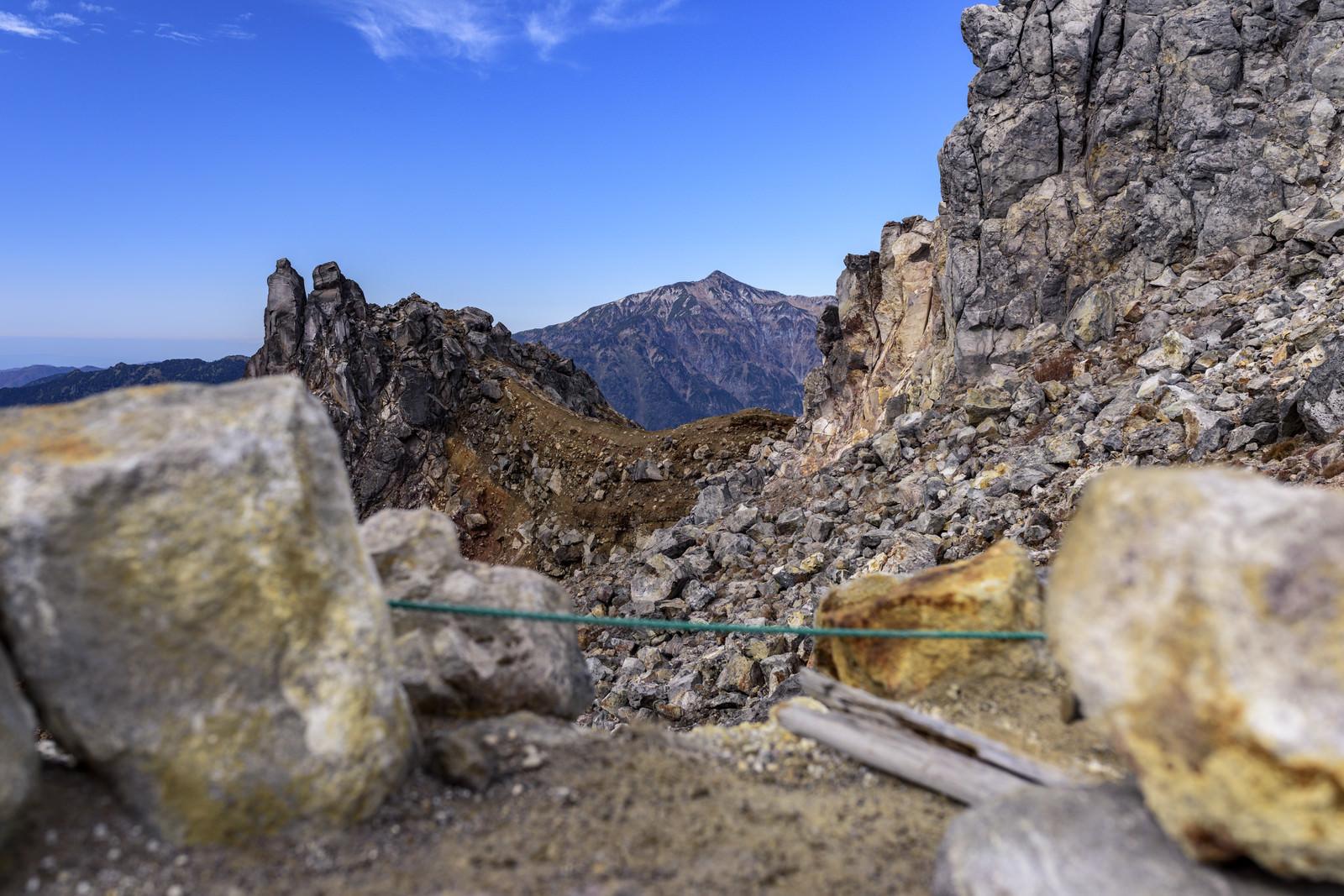 「焼岳から見る笠ヶ岳の岩とロープ(かさがたけ)」の写真